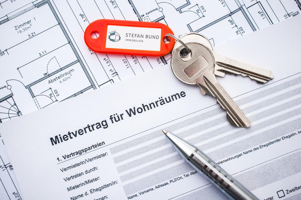 Mietvertrag für Wohnräume mit Schlüssel und Kugelschreiber